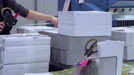 ofset : unrecognizable woman working at print factory packs printed products for shipment