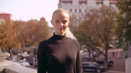 символы : portrait blonde in town female with blond hair posing. girl looking at the camera on the background city landscape in autumn Стоковые видеозаписи