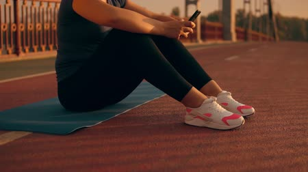 oran : unrecognizable jogger sitting on the yoga mat using smartphone after stretching. woman wearing sneakers white and pink colors