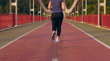 кроссовки : unrecognizable woman with short haircut wearing sports clothes running on the bridge at sunny day pan slow motion Стоковые видеозаписи