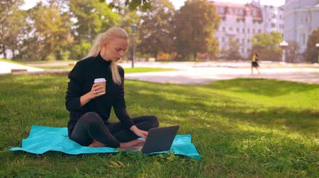 netbook : young caucasian woman with blond long hair typing on laptop drinking coffee to go sitting on the lawn with green grass. on the background sunny cityscape