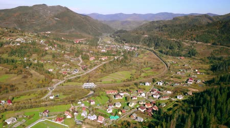 karpaty : aerial view of a small town in the mountains, houses, railroad traveling train, football field with people playing