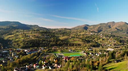 drone flies over the playing field in small city in mountainous area sunny day in autumn season