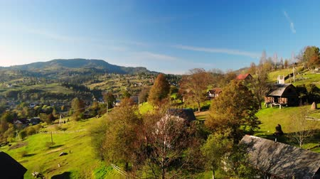 drone flies over rural houses in the carpathians autumn season landscape sunny day on the background mountains and pinewood