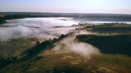 drone flying over rolling hills in the early morning mist summer season