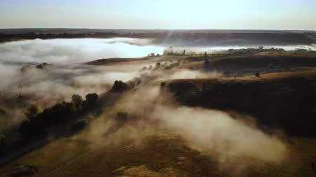 drone flying forward over rolling hills in the early morning mist autumn season