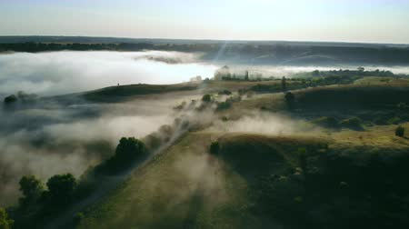 drone flying back over rolling hills in the early morning mist summer season Стоковые видеозаписи