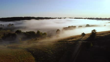 drone flies into the fog over rolling hills in autumn season morning landscape in countryside