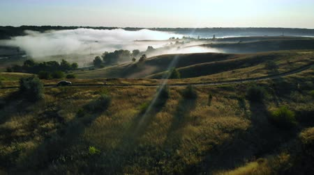 drone flying over rolling hills with mist amazing sunrise in summer time