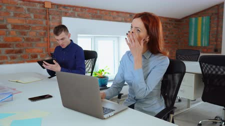 business people working using computer sitting at the desk in office with casual interior. redhead businesswoman typing on laptop businessman holding digital tablet 動画素材