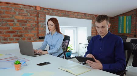 two young employees in startup company sitting at the desk in office with casual interior. redhead businesswoman typing on laptop businessman holding digital tablet Стоковые видеозаписи