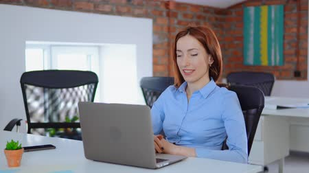 young manager with red hair using webcam on laptop has online meeting sitting at the white desk in loft office professional redhead business woman use app for call on computer at work daytime.