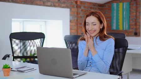 young successful manager with red hair looking on screen laptop reading great news raising hands celebrating success sitting at the white desk in loft office professional redhead business woman showing positive emotions work daytime.