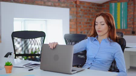 young exhausted manager with red hair using closed laptop and resting sitting at the white desk in loft office professional redhead business woman tired and worn out work daytime.