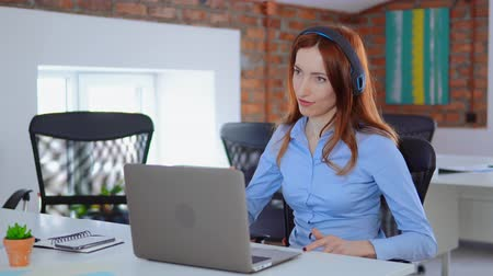 young manager with red hair has a break listening music using headphones dancing sitting at the white desk in loft office professional redhead business woman showing positive emotions relaxing at work daytime.