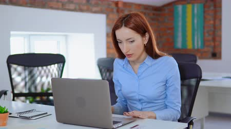 young manager with red hair sitting at the white desk in loft office professional redhead business woman holding credit card looking on screen computer happy shopping at work daytime. Vídeos