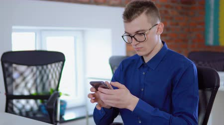 munkáltató : portrait young worker in startup company using app on smartphone or checking email sitting in loft office businessman chatting online at work daytime Stock mozgókép