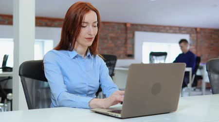 young adult employee sitting at the white desk in open space office startup company. redhead business woman typing on laptop looking on display computer. on the background co workers works