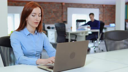 redhead business woman typing on laptop looking to the camera with beautiful friendly smile.young adult employee sitting at the white desk in open space office startup company. on the background co workers works