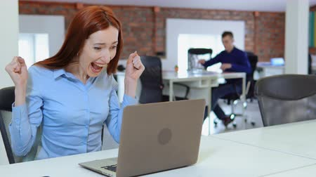 young adult employee celebrating victory sitting at the white desk in open space office startup company. redhead business woman reading great news looking on display computer background co workers works