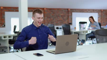 caucasian employee raising hands celebrating win sitting at the white desk in open space office startup company. young business man typing on laptop looking on display computer. on the background cowo