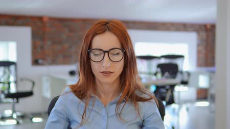 мысли : Businesswoman wearing glasses and blue shirt. An idea comes to her head. Стоковые видеозаписи