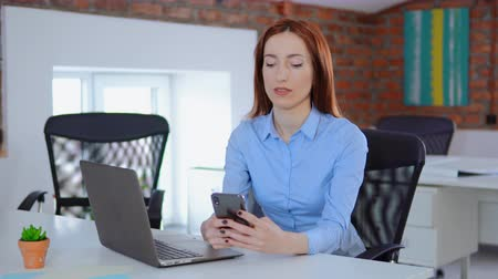 Beautiful mature woman writing a text on smart phone. Serious female adult checking email and typing on cellphone at workplace. Стоковые видеозаписи