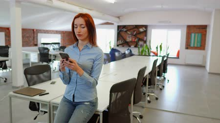Strong independent woman in co-working space. Female worker sits on the desk while texting and smiling. Стоковые видеозаписи