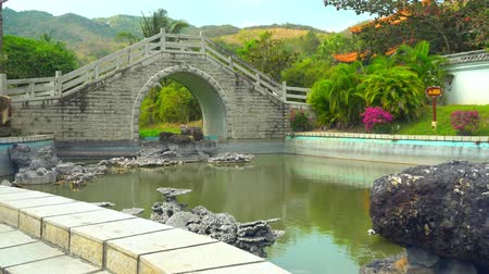 Picturesque little bridge across the river. Nature of South China during daytime.