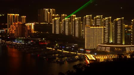Brightly illuminated Sanya dock. Riverside bay bridge panorama.