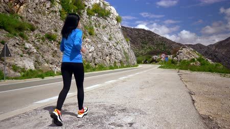 pista de corridas : back view woman running outdoors. runner wearing bright sportswear jogging along road in mountain area