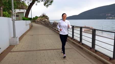 zweten : happy brunette woman jogging along seashore in montenegro. jogger wearing white hoodie enjoy cool spring weather Stockvideo