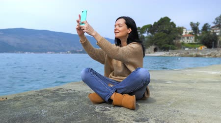 alma : beautiful woman sitting on the seacoast using smartphone taking selfie photo outdoors. happy girl posing for photo on the background beautiful view on sea and mountains smiling female with long hair