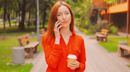 ouvido : Girl Having Phone Conversation While Walking In Green Street Park. Having Coffee And Smiling. Heard Good News.