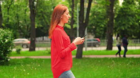 рыжеволосый : Young Woman Going by Road and Looking in Smartphone. Beautiful Female Texting Messages in Mobile Walking in Beautiful Green Park. Стоковые видеозаписи