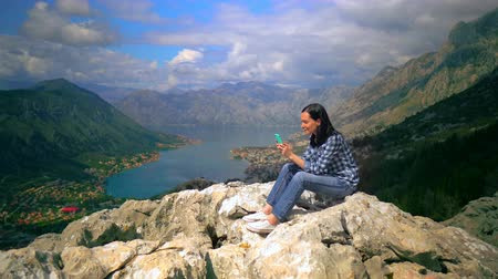 facetime : Beautiful Summer Scenery of Lake and Mountains. Woman Sitting on Mountain Top and Tapping Messages in Smartphone. Small Town on Background.