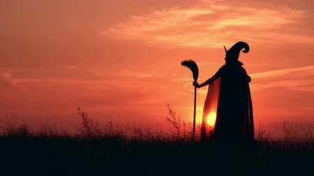 hůlky : sorceress standing on the hill straightens hat looking on amazing sky with upward sun