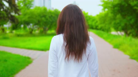 without face : back view woman with long hair walking in city with green trees and modern buildings on the background