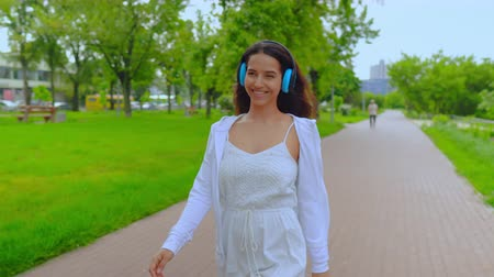 playlist : student listening music via headphones cheerful girl walks in city park with lake enjoy favorite song