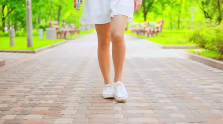színésznő : close up details female legs woman wearing white dress and casual sneakers walking on the street