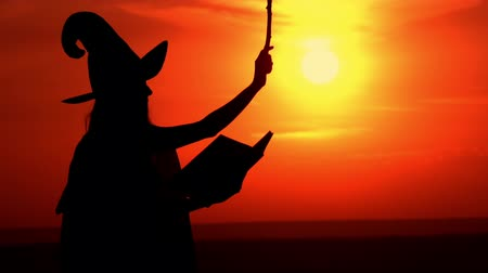 czary : outdoors silhouette sorceress wearing fancy dress and hat reading spell from book view on the sky with upward sun