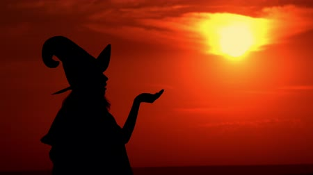 hag : outdoors silhouette sorceress conjures with a potion wearing fancy dress and hat at sunrise Stock Footage