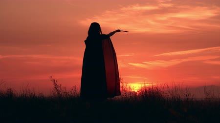 upward : back view woman wearing costume sorceress holding magic wand outdoors silhouette warm sky with rising sun Stock Footage