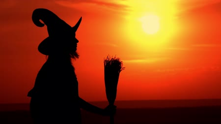 hag : witch holding broom looking on the amazing red sky with orient sun standing on the hill Stock Footage