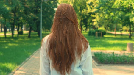 színésznő : portrait caucasian woman with long red hair walking in the park turn to the camera with happy smile Stock mozgókép