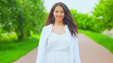 actrice : view on the young woman walks in the city park on the background with green nature and modern building cheerful girl enjoy stroll in spring day Stockvideo
