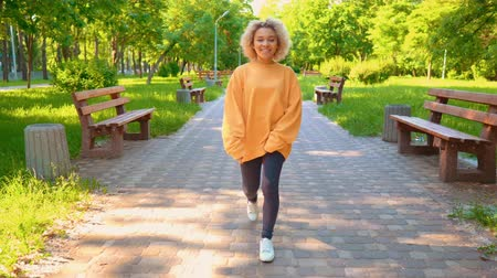 on the go : front view happy young woman walking to the camera smiling female wearing yellow sweater and denim stroll in city park at sunny day