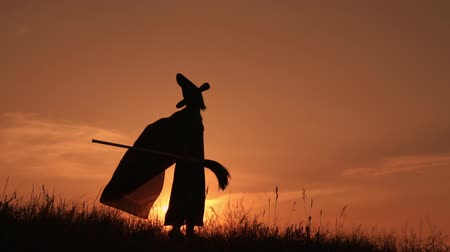 süpürge : Silhouette of a witch in a raincoat and a hat at sunset she performs a ritual dance. In the hands of holding a flying broom.