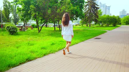 goes : back view brunette wearing white dress and hoodie walking in modern town with green nature casual female going by the green trees on the background heavy traffic and city scape