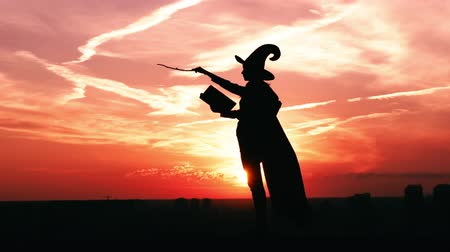chapeau sorciere : silhouette woman in hat and holding big magic book and wand outdoors side view girl in a witch costume read spell book cityscape slow motion
